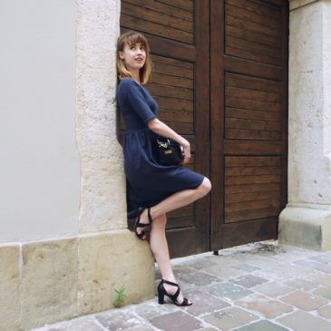 Elegancka granatowa sukienka w towarzystwie czarnych dodatków